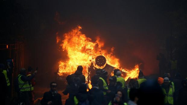 A car burns as protesters gather by Place de l'Etoile. Photo: Reuters