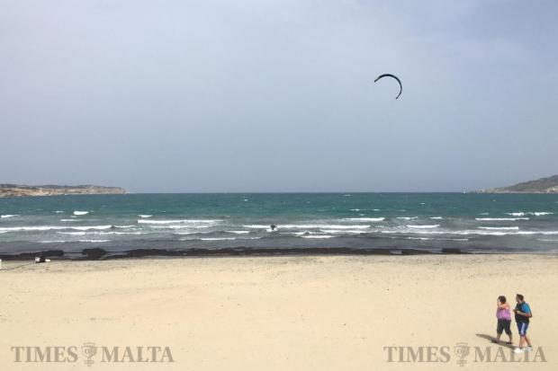 A couple walk along the beach in Mellieha as a kite surfer makes the most of the north-easterly wind on April 6. Photo: Matthew Mirabelli