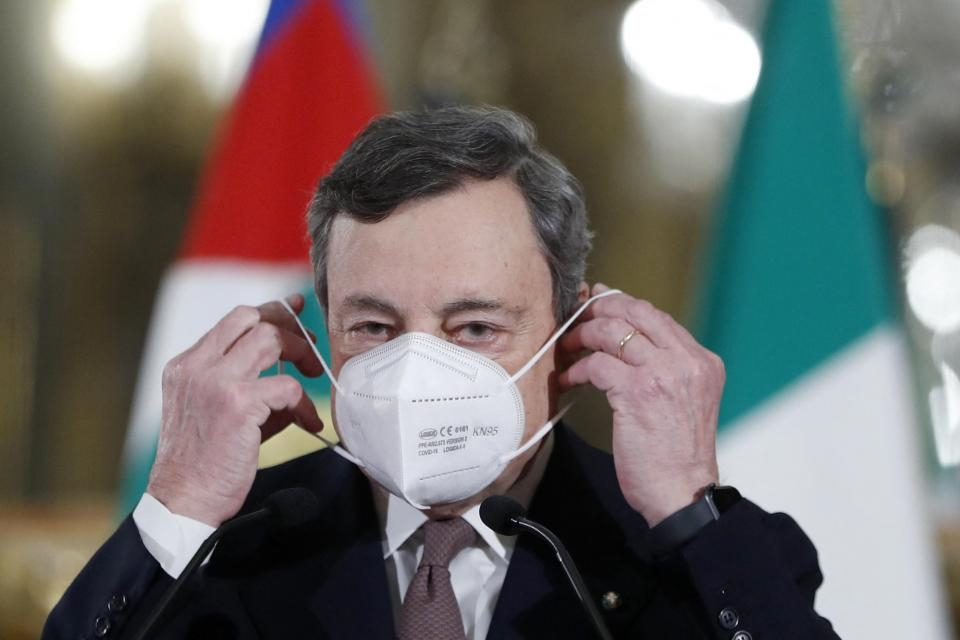 Italy's new prime minister, former European Central Bank President Mario Draghi puts on his face mask after addressing the media on February 12, 2021. Photo: AFP