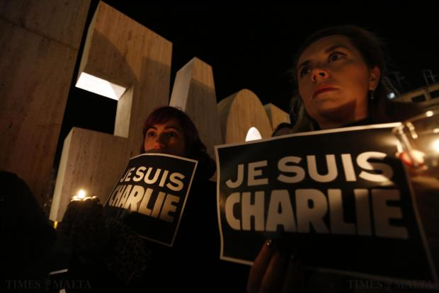 "People hold candles and placards reading ""I Am Charlie"" during a vigil paying tribute to victims in St Julian's on January 8, following a shooting by gunmen at the offices of weekly satirical magazine Charlie Hebdo in Paris. Photo: Darrin Zammit Lupi"