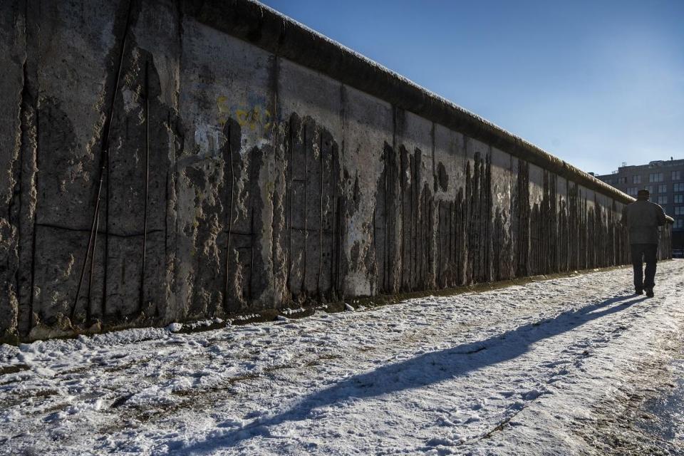 Un hombre camina sobre la nieve a lo largo de un tramo conservado del muro de Berlín.  Foto de archivo AFP