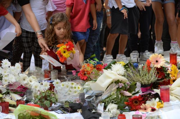 Children lay flowers at the Great Siege Monument in Valletta on October 22 during a national rally attended by thousands in the capital after blogger Daphne Caruana Galzia was murdered outside her home after a car bomb went off on October 16. Photo: Matthew Mirabelli