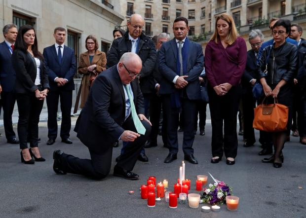 Mr Timmermans knees at a candlelight vigil for Ms Caruana Galizia held in Brussels. Photo: Reuters
