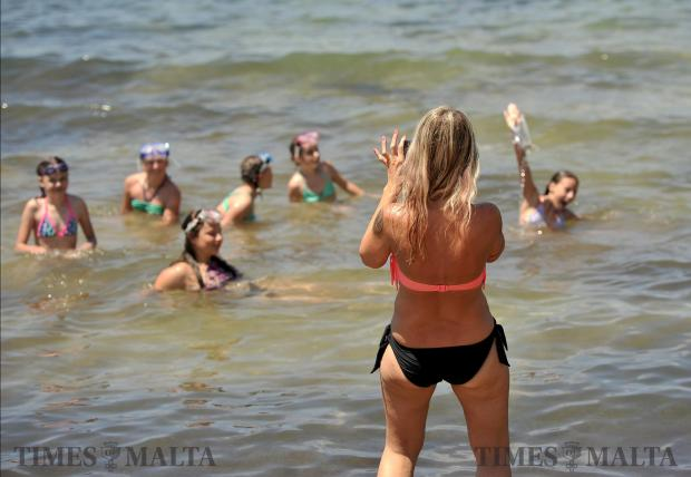A woman takes a photo of children bathing in Golden Bay on June 21. Photo: Chris Sant Fournier