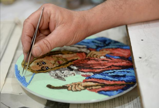 A grain of rice is carefully placed on a plate in preparation for an Easter exhibition by a member of the Domus Pius IX Society at their premises in Cospicua on March 31. Photo: Matthew Mirabelli
