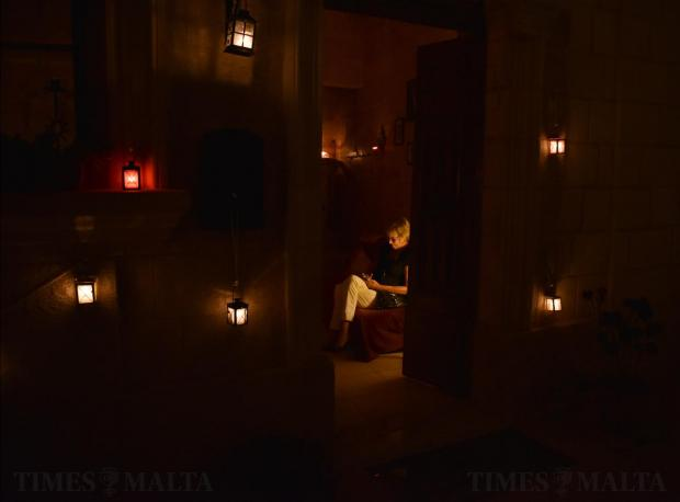 A woman reads a book in her house whilst candles hang on her façade during the annual Birgu by Candlelight in Vittoriosa on October 15. Photo: Mark Zammit Cordina