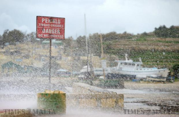 Waves crash into the road in St Thomas Bay, as strong easterly winds hit the island on December 16. Photo: Matthew Mirabelli