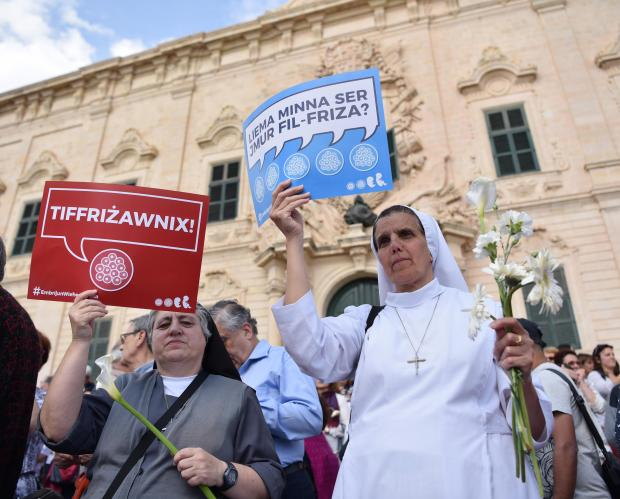 nuns hold up placards outside the Prime Ministers' office during a protest against a bill introducing embryo freezing in Valletta on April 22. Photo: Mark Zammit Cordina