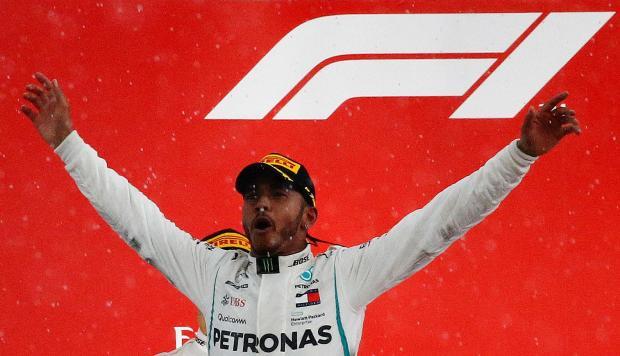 Mercedes' Lewis Hamilton celebrates on the podium after winning the race.