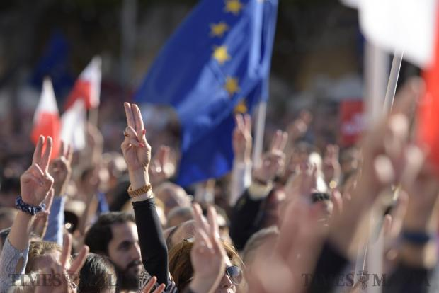 People attending an anti-corruption protest lift their hands showing the peace sign in Valletta on April 23. Photo: Mark Zammit Cordina