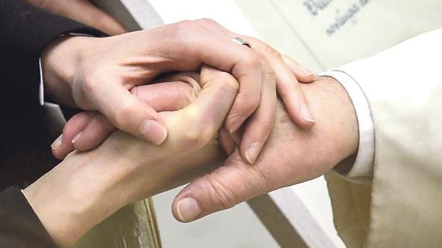 A worshiper (left) holds Pope Francis' hand. Photo: Tiziana Fabi/AFP