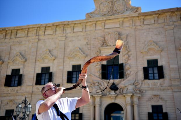 A man plays a shofar in front of the Auberge de Castille in Valletta on July 14. Made from a ram's horn, the shofar is used in Jewish religious ceremonies. Photo: Mark Zammit Cordina