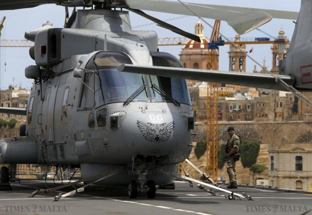 A British Royal Marine commando patrols near a Merlin helicopter on the flight deck of the Royal Navy ship HMS Bulwark at the Palumbo Shipyards on June 12. HMS Bulwark arrived at Palumbo Shipyards on Friday morning for engineering work and for its sailors and marines to enjoy an operational five-day stand-down after saving nearly 3,000 migrants in the Mediterranean in an intensive three-week patrol. Photo: Darrin Zammit Lupi