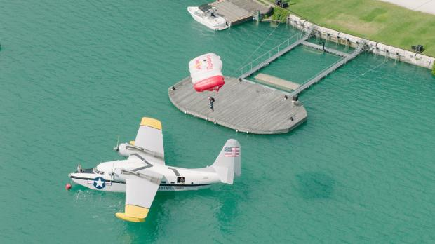 Parachutist leaps from seaplane and lands back on its wing
