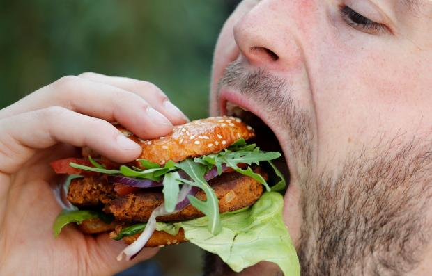 """Max Kraemer of food maker """"Bug Foundation"""" bites into an insect hamburger in Aachen"""