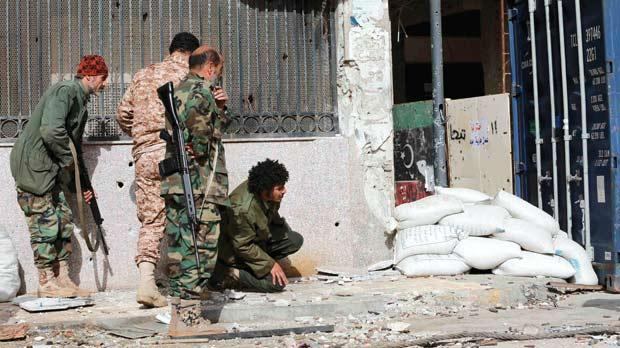 Members of the Libyan pro-government forces, backed by locals, take up positions during clashes with the Shura Council of Libyan Revolutionaries, an alliance of former anti-Gaddafi rebels, who have joined forces with Islamist group Ansar al-Sharia, near Benghazi port.