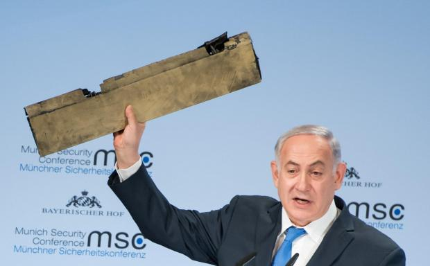 sraeli Prime Minister Benjamin Netanyahu holds up a remnant of what he said was a piece of Iranian drone which was shot down in Israeli airspace.