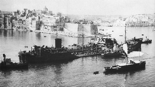 The SS Ohio enters the Grand Harbour under the control of dockyard tugs and with HMS Ledbury still secured to her side.