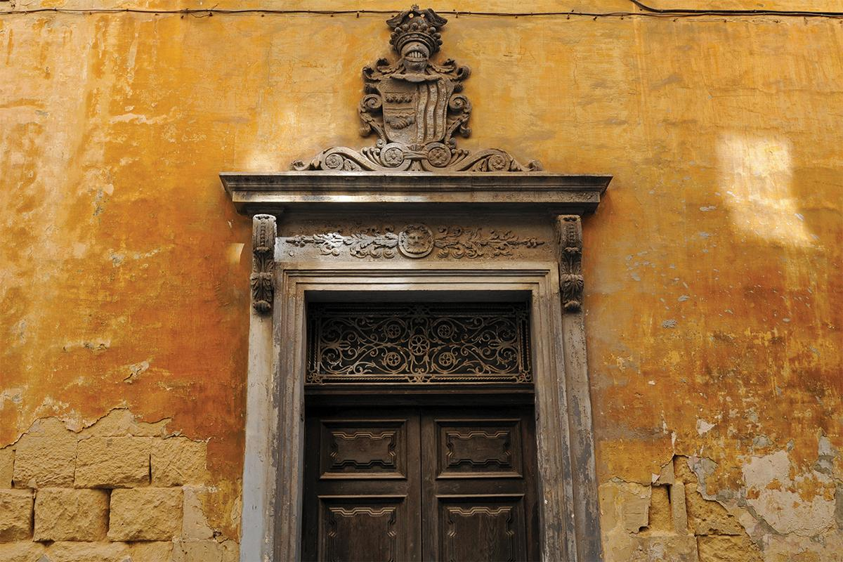 An ornate doorway in Valletta, featuring a coat of arms above the cornice. Photo: Shutterstock.com