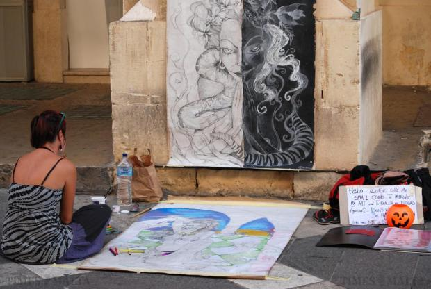 "An artist displays drawings next to the arches in Republic Street, Valletta, with a sign asking the public to give small change to improve her art on October 8. She was also happy with ""just a smile"". Photo: Mark Zammit Cordina"
