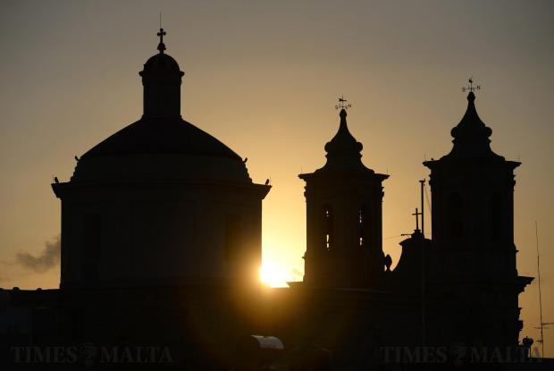 The sun sets behind the parish church in Gharghur on October 31. Photo: Matthew Mirabelli
