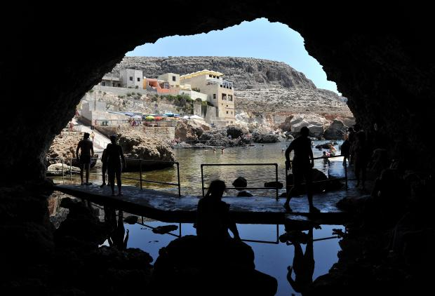 Bathers take shelter from the scorching sun in a cave at Ghar Lapsi on July 19. Photo: Chris Sant Fournier