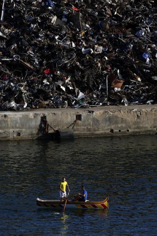 Rowers train for the September 8 regatta against a backdrop of scrapped material at Laboratory Wharf in Grand Harbour on August 29. Photo: Darrin Zammit Lupi
