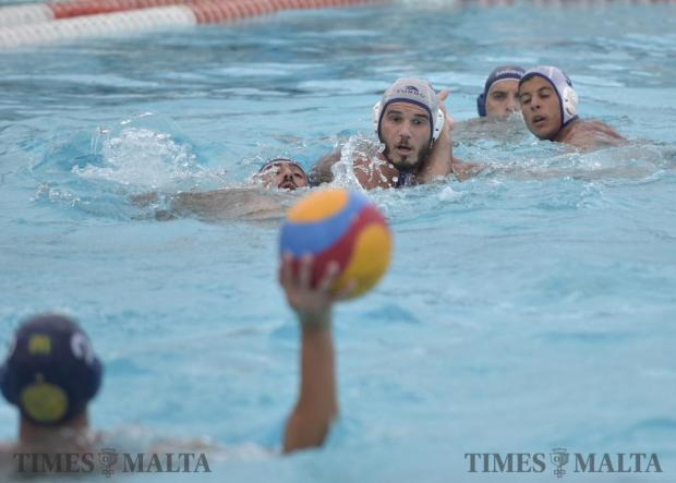 Valletta's James Spiteri Staines attempts to pass the ball to his teammate whilst Exiles' Sean Gravina tries to defend the area during their waterpolo match at the National Pool in Tal-Qroqq on August 22. Photo: Mark Zammit Cordina