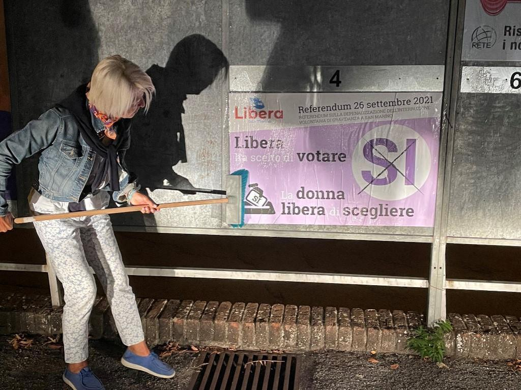 Pro-abortion campaigner, and doctor, Francesca Nicolini puts up posters on the night of September 9, 2021 in San Marino at the start of the campaign for the September 26 referendum on the legalisation of abortion.
