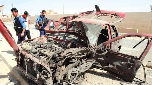 Policemen inspecting a destroyed car after a car bomb attack near a police station, south of the city of Kirkuk, yesterday. At least eight people were wounded in the attack, police said. Photo: Reuters