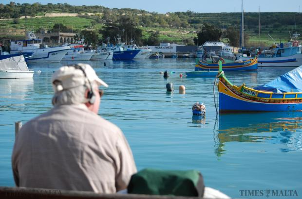 A man relaxes and enjoys the view on a beautiful day at the picturesque fishing village of Marsaxlokk on January 13 . Photo: Mark Zammit Cordina