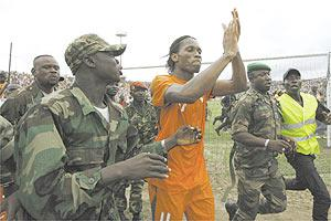 Ivory Coast`s Didier Drogba is escorted by soldiers during a victory lap in Bouake on Sunday.