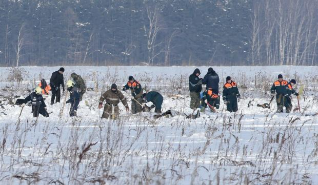 Russian Emergency Situations Ministry members work at the crash site of the AN-148 airplane in Moscow region.