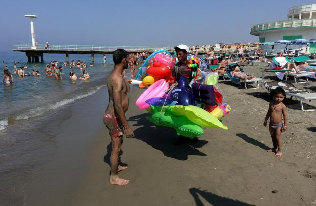 People cool off at the beach in Italy
