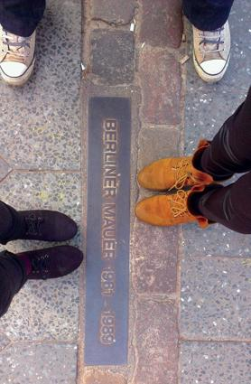 Straddling the Berlin Wall's remains.