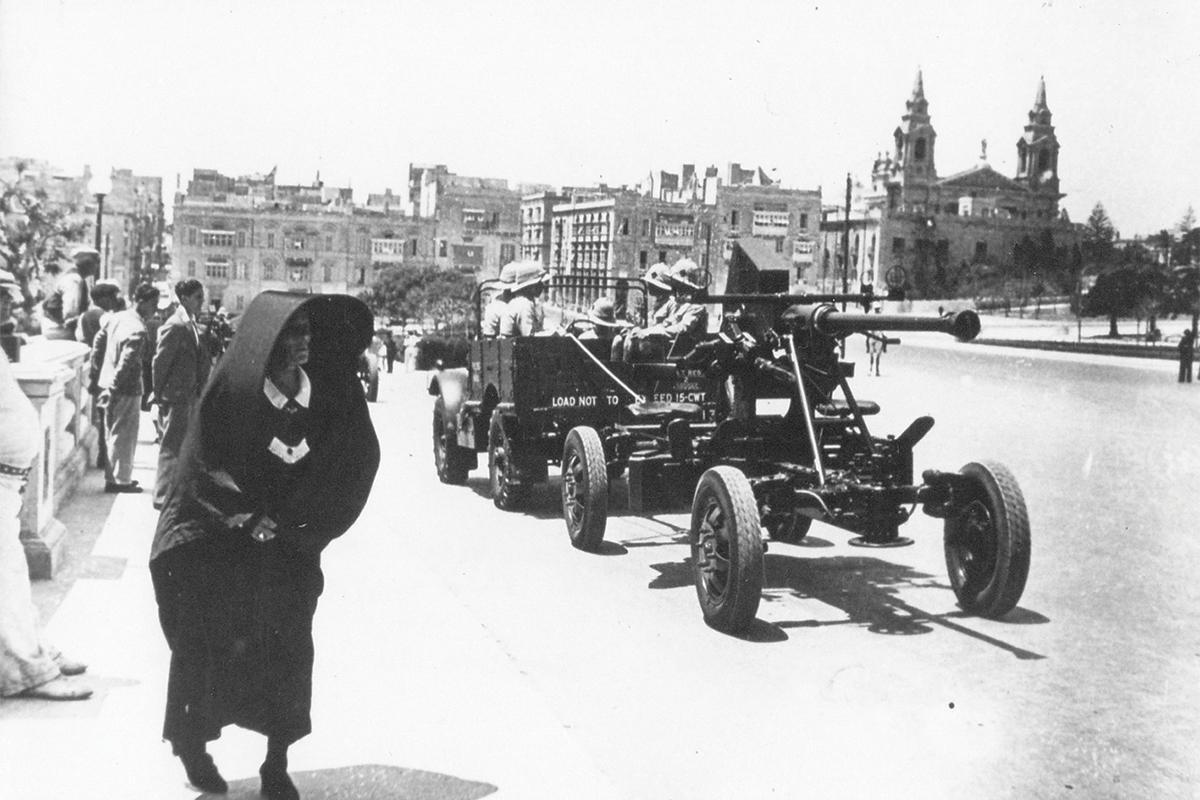 A military vehicle pulling a 40mm Bofors Light Anti-Aircraft Gun down Giloramo Cassar Avenue, Valletta.