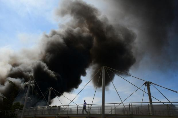 A man walks over a bridge to see the fire at the Sant Antnin recycling plant in Marsascala on May 22. Photo: Jonathan Borg