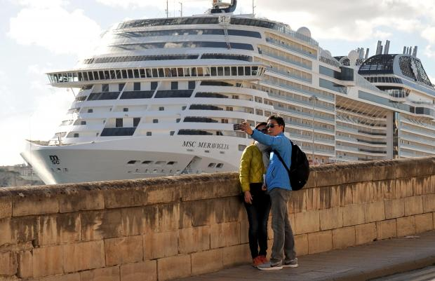 Tourists take a selfie with 'their' cruise liner as a backdrop in Grand Harbour on December 6. Photo: Chris Sant Fournier