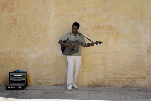 A busker plays his guitar at City Gate in Valletta on August18. Photo Mark Zammit Cordina