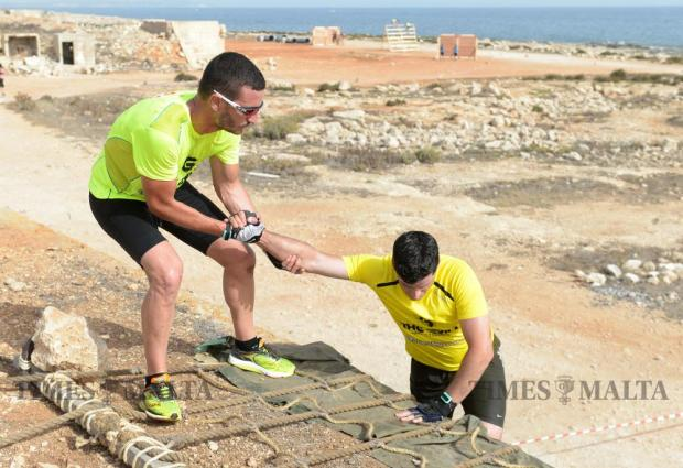 A participant helps his teammate at the top of a rope ladder whilst taking part in The Grid obstacle course race in Pembroke on May 29. The race, the first of its kind in Malta, covered 15km and included over 30 obstacles. Photo: Matthew Mirabelli