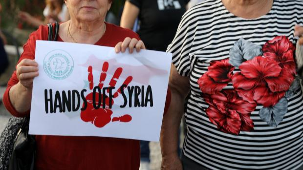 A left wing protestor holds a placard during a demonstration against air strikes on Syria by the United States, Britain and France, outside the American Embassy in Nicosia.
