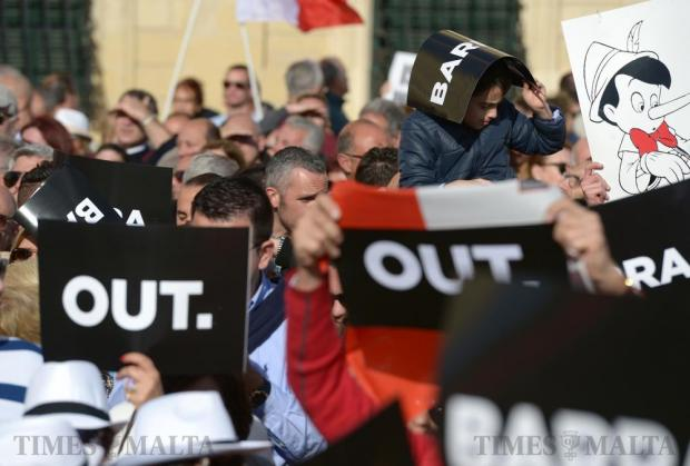 Protestors hold up placards during a demonstration calling for the resignation of the Prime Minister and two members of the government following the Panama Papers leak scandal outside Castille in Valletta on April 10. Photo: Matthew Mirabelli