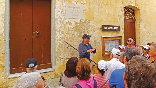 Joe Agius giving information to the Ramblers' group outside a house where painter Mattia Preti once resided.