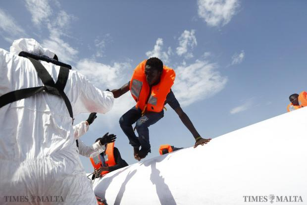 A migrant jumps from a rubber dinghy to a Migrant Offshore Aid Station (MOAS) RHIB (Rigid-hulled inflatable boat) before being taken to the MOAS ship MV Phoenix some 32 kilometres off the coast of Libya on August 3. 118 migrants were rescued from a rubber dinghy off Libya on Monday morning. The Phoenix, manned by personnel from international non-governmental organisations Medecins san Frontiere (MSF) and MOAS, is the first privately funded vessel to operate in the Mediterranean. Photo: Darrin Zammit Lupi
