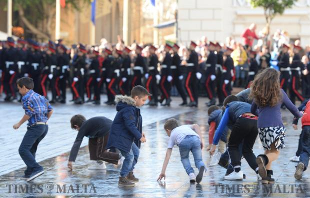 Children try to gather empty rifle cartridges after the AFM parade in St George's Square, Valletta to celebrate Republic Day on December 13. Photo: Matthew Mirabelli