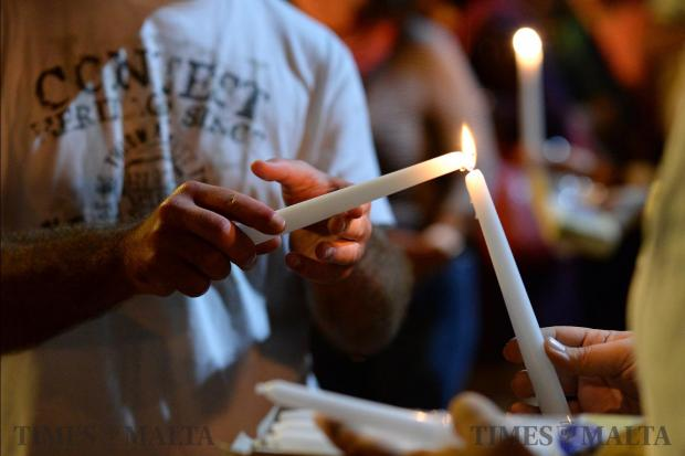 A man lights a candle during a candlelight vigil in Sliema on October 16, in tribute to late journalist Daphne Caruana Galizia who was killed by a car bomb close to her home in Bidnija. Photo: Matthew Mirabelli