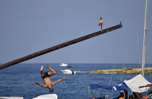 A competitor backflips from the greasy pole after not managing to grab the flag at the annual gostra festival held in St Julian's on 30 August. Photo: Mark Zammit Cordina