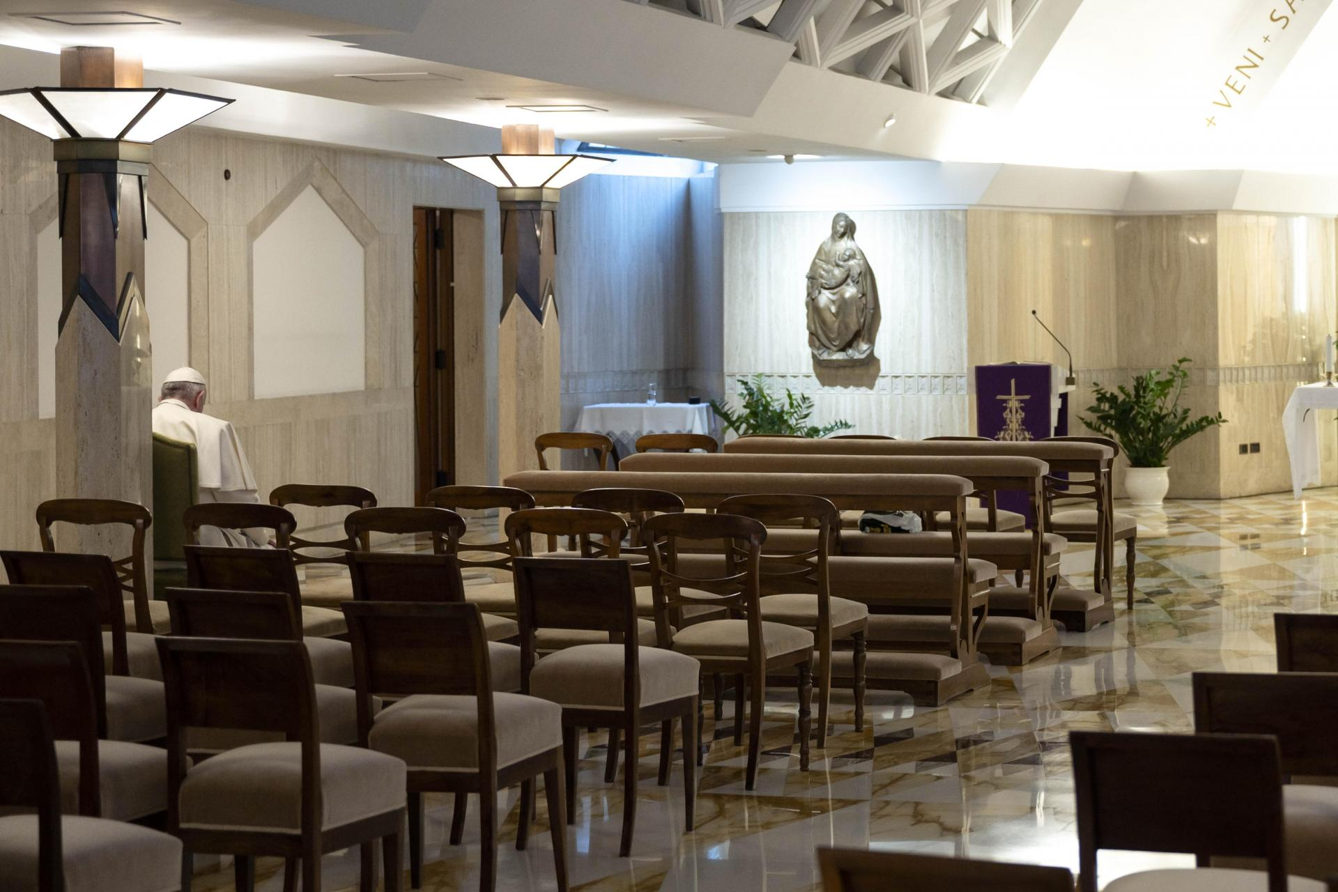 Pope Francis (Rear L) gathering his thoughts while celebrating a daily mass alone in the Santa Marta chapel at the Vatican.