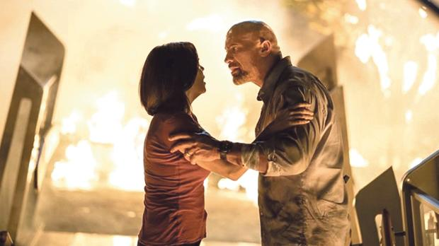 Dwayne Johnson risks his life and limb to save Neve Campbell in Skyscraper.