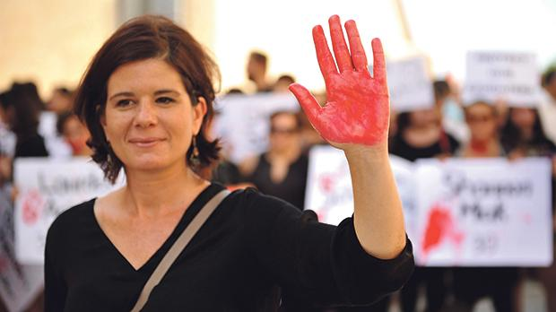 Lara Dimitrijovic, director of the Women's Rights Foundation, raising a bloody hand yesterday, symbolising the murder of women. Photo: Chris Sant Fournier